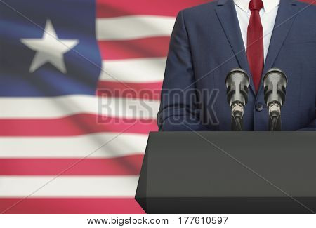 Businessman Or Politician Making Speech From Behind A Pulpit With National Flag On Background - Libe
