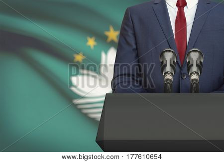 Businessman Or Politician Making Speech From Behind A Pulpit With National Flag On Background - Maca