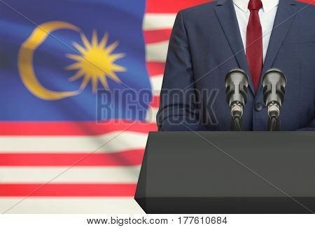 Businessman Or Politician Making Speech From Behind A Pulpit With National Flag On Background - Mala