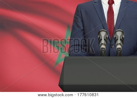 Businessman Or Politician Making Speech From Behind A Pulpit With National Flag On Background - Moro