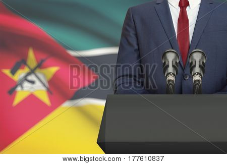 Businessman Or Politician Making Speech From Behind A Pulpit With National Flag On Background - Moza
