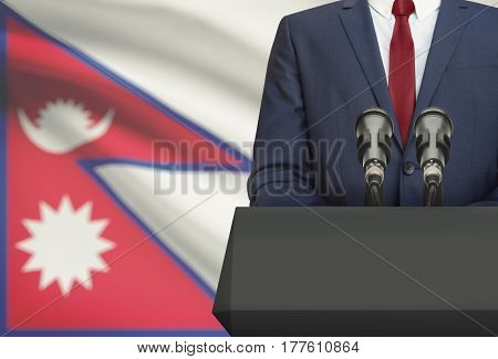 Businessman Or Politician Making Speech From Behind A Pulpit With National Flag On Background - Nepa