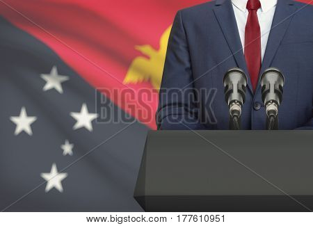 Businessman Or Politician Making Speech From Behind A Pulpit With National Flag On Background - Papu