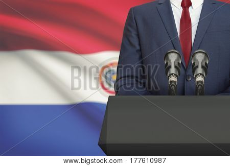 Businessman Or Politician Making Speech From Behind A Pulpit With National Flag On Background - Para