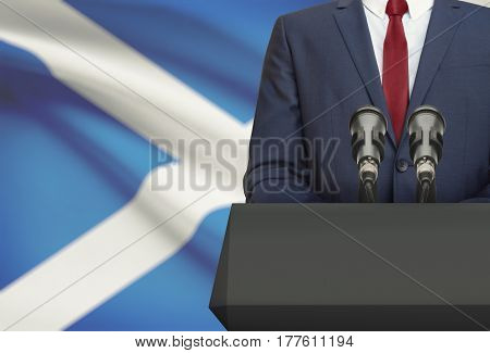 Businessman Or Politician Making Speech From Behind A Pulpit With National Flag On Background - Scot