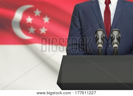 Businessman Or Politician Making Speech From Behind A Pulpit With National Flag On Background - Sing
