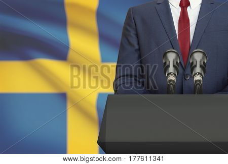 Businessman Or Politician Making Speech From Behind A Pulpit With National Flag On Background - Swed