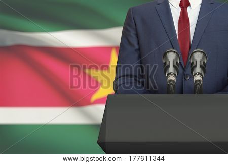 Businessman Or Politician Making Speech From Behind A Pulpit With National Flag On Background - Suri