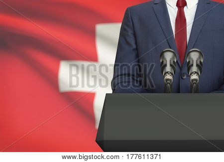 Businessman Or Politician Making Speech From Behind A Pulpit With National Flag On Background - Swit