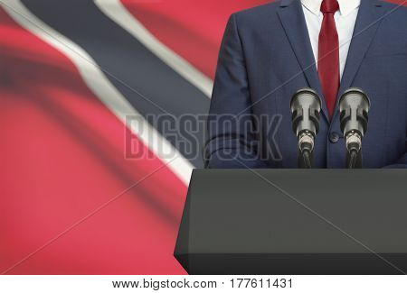 Businessman Or Politician Making Speech From Behind A Pulpit With National Flag On Background - Trin