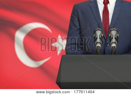 Businessman Or Politician Making Speech From Behind A Pulpit With National Flag On Background - Turk