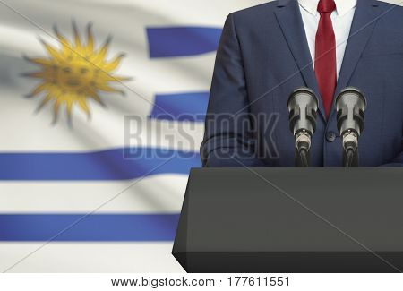 Businessman Or Politician Making Speech From Behind A Pulpit With National Flag On Background - Urug