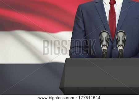 Businessman Or Politician Making Speech From Behind A Pulpit With National Flag On Background - Yeme