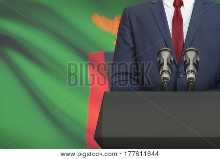 Businessman Or Politician Making Speech From Behind A Pulpit With National Flag On Background - Zamb
