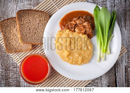 peas cooked with meat sauce and ramsons on a wooden table