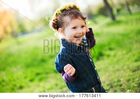 The little girl laughs. Girl running on green grass in the spring. The child on the head with a wreath of yellow flowers dandelions. Free space.