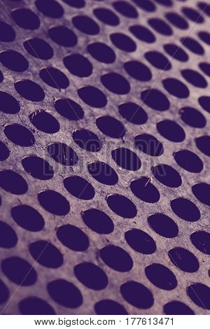 Dirty metal sheet with perforations. Purple colored