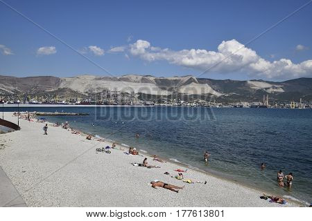 City Beach Town Of Novorossiysk. Cargo Port With Port Cranes. Sea Bay And Mountainous Coast.