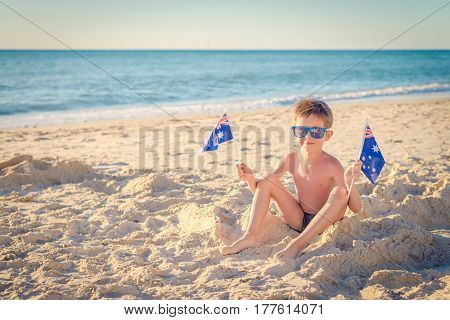 Cute smiling boy sitting on the beach and holding Australian flags on Australia day