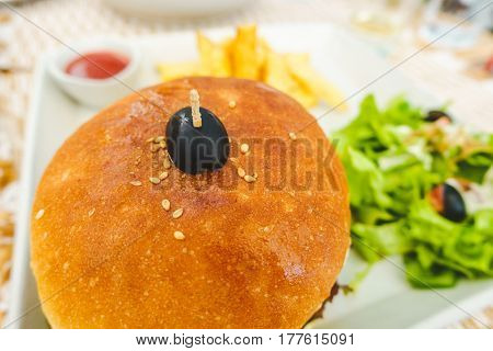Burger served with salad, chips and tomato ketchup