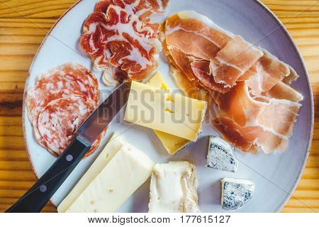 Plate with a variety of Italian cheese and charcuterie, on a wooden table
