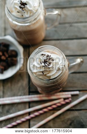 Top View Of Iced Chocolate With Milk In Retro Glass Jar (mason Jar), Pink Straw And Candy On Wooden