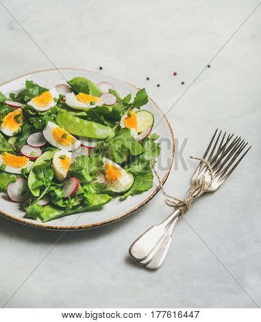 Healthy spring green salad with radish, boiled egg, arugula, green pea and mint in white plate over grey marble background, selective focus