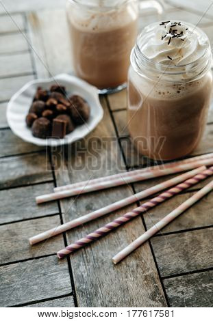Iced Chocolate With Milk In Retro Glass Jar (mason Jar), Pink Straw And Candy On Wooden Table.