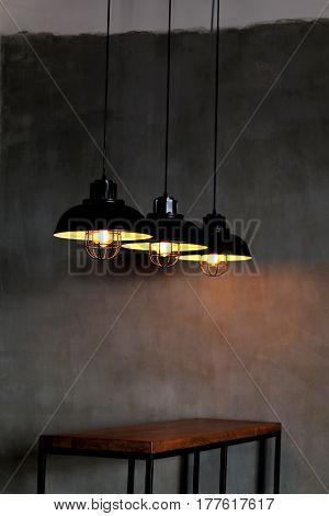 grey Room with three lamps Hanging over a wooden table. The Ceiling Fixture on wall background.