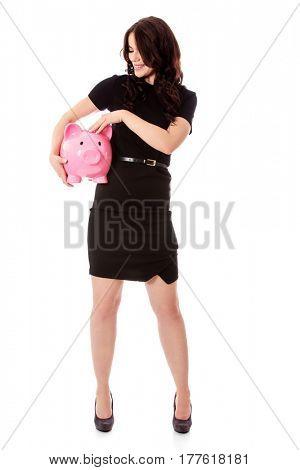 Happy businesswoman saving money in piggybank