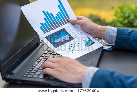 Handsome Businessman Wearing Suit And Using Modern Laptop Outdoors And Graph Finance Diagram.
