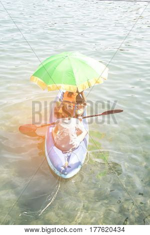 Teenage boy and girl row the boat under sunshine