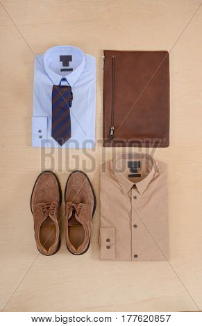 Men's casual outfits with man shirt clothing and accessories on wooden background,