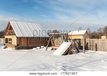 Rural courtyard with children's playground in winter