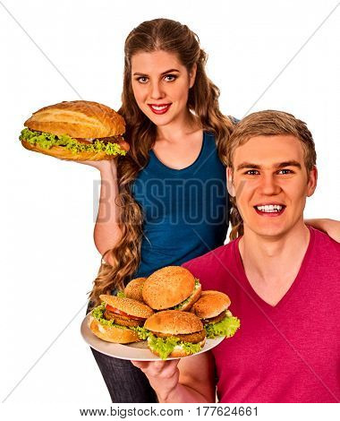 Couple eating fast food. Man and woman eat hamburger with ham . Friends holding two burder junk and offer treats on white background isolated.