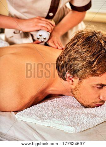 Man back massage beauty salon. Electric stimulation man skin care . Professional equipment microcurrent body lift . Anti aging rejuvenation . Man receiving electroporation skin care therapy .