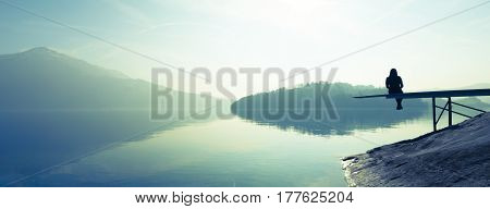 Woman sitting on the shore of the lake. Clear sunny day. Monochrome.