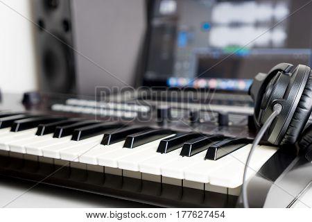Synthesizer keyboard and headphone lying on Music studio working desktop