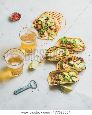 Healthy corn tortillas with grilled chicken fillet, avocado, fresh salsa, limes, beer in glasses over light grey marble background, selective focus. Gluten-free, weight loss, allergy-friendly concept