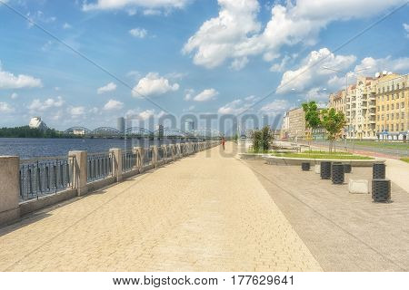 Cyclists ride on the Sunny quay on the Daugava river in Riga in the summer on the background of the bridges