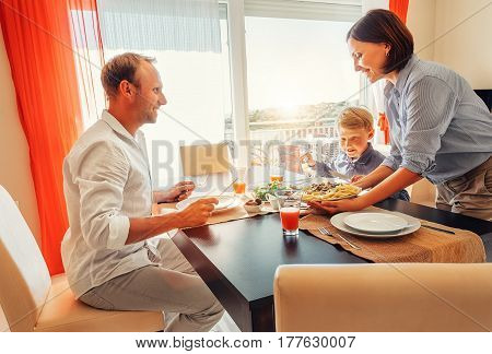 Mother brings a dish of meal at table to her hungry family
