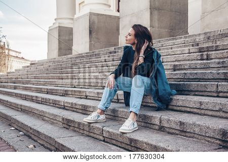 Fashion model wearing ripped boyfriend jeans, jacket and sneakers posing in the city street. Fashion urban outfit. Casual everyday clothing style.