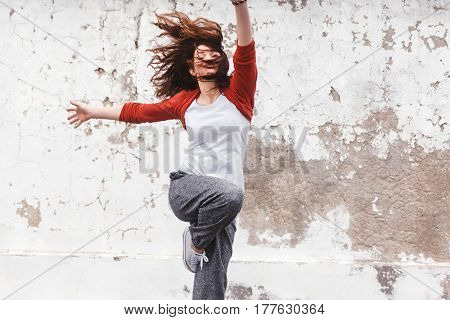 Fitness sport girl in fashion sportswear jumping and dancing hip hop by the street wall, outdoor sports, urban style