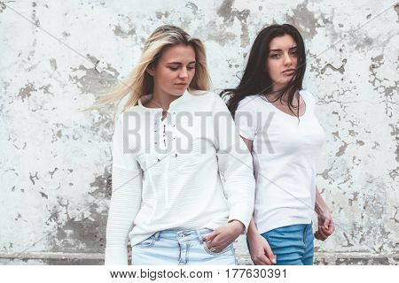 Two young models, blond and brunette, wearing blank white tshirt and jeans posing against rough street wall, fashion urban clothing style, mockup for t-shirt print store