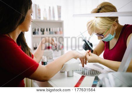 Woman at beauty salon enjoying manicurist treatment