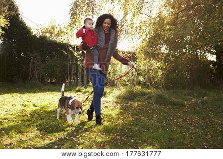 Mother With Child Taking Dog For Walk In Autumn Garden