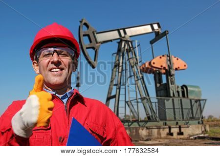 Oil Worker Gesturing Thumb Up Next to Pump Jack. Portrait of a smiling worker.
