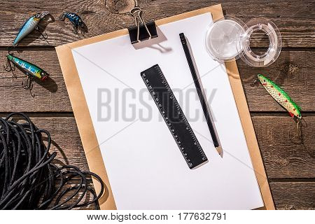 Accessories for fishing on the background of wood. Reel, fishing line, float, net hooks, lures for fishing. Top view. Still life. Copy space