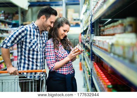 Couple using trolley shopping in store for food and ingridients