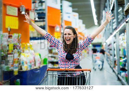 Shopaholic woman enjoying shopping spree in supermarket